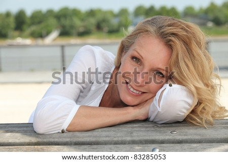 Relaxed happy woman sitting on the waterfront