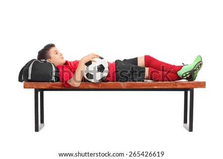 Relaxed little boy in a red football jersey lying on a wooden bench and holding a ball isolated on white background