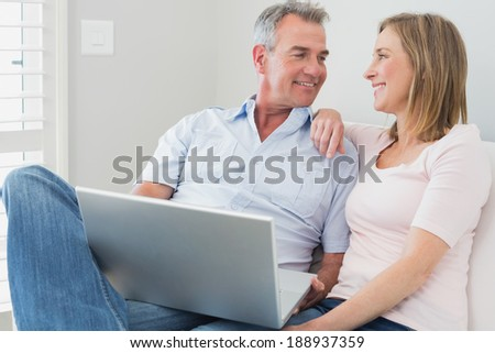 Relaxed loving couple using laptop on sofa at home