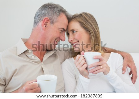 Relaxed loving couple with coffee cups in living room at home - stock photo