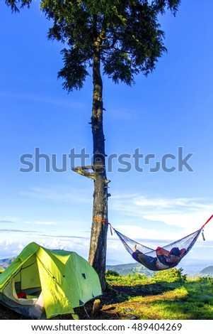 Relaxed man and lying in a comfortable hammock during camping with blue sky