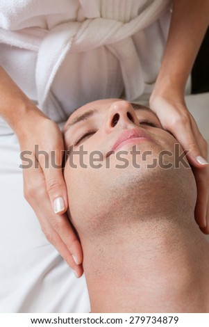 Relaxed man gets a massage - stock photo