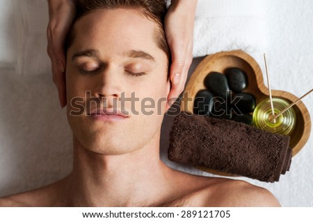 Relaxed man getting a face  massage at day spa - stock photo