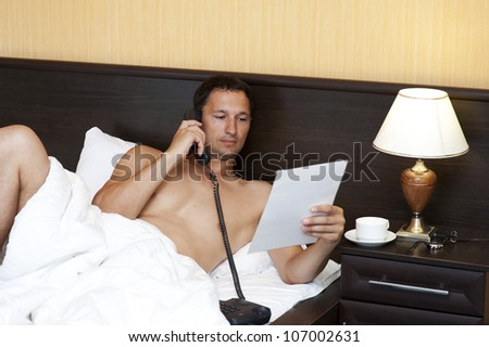 Relaxed Man in Bed, hotel or domestic room calling by phone - stock photo