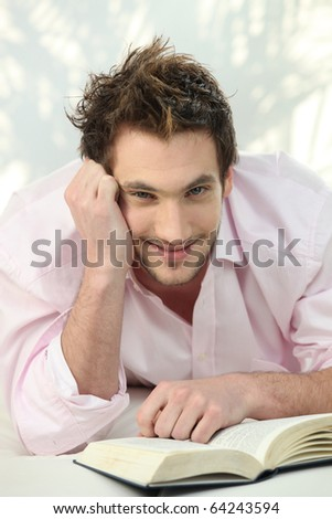 Relaxed man in front of a book - stock photo