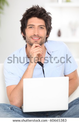 Relaxed man in front of a laptop computer - stock photo