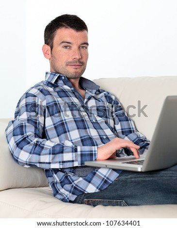 relaxed man on sofa with computer - stock photo