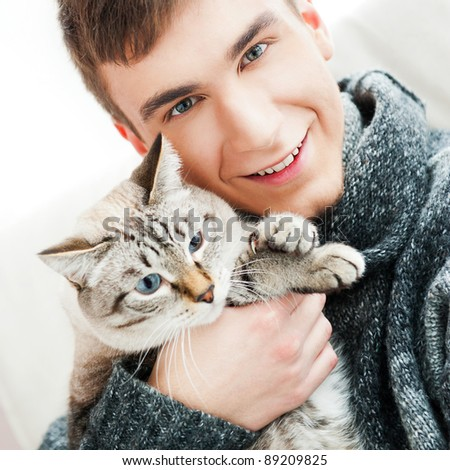 Relaxed man sitting on armchair holding and petting pet cat - stock photo