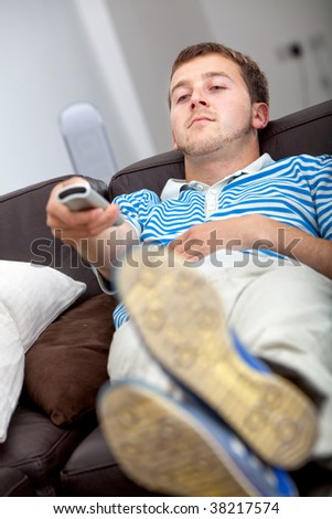 Relaxed man with a remote control watching tv - stock photo