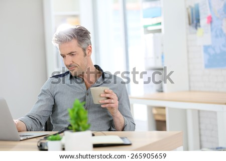 Relaxed man working form home on laptop - stock photo
