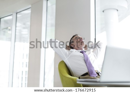 Relaxed mature businessman reclining at lobby - stock photo