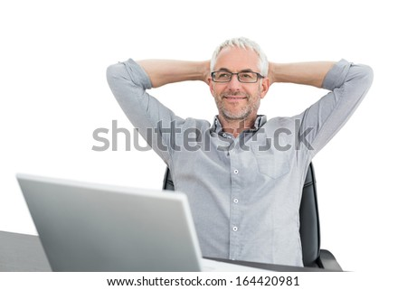 Relaxed mature businessman sitting with hands behind head and laptop against white background