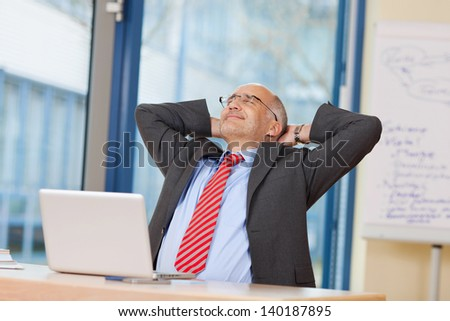 Relaxed mature businessman with hands behind head at office desk - stock photo