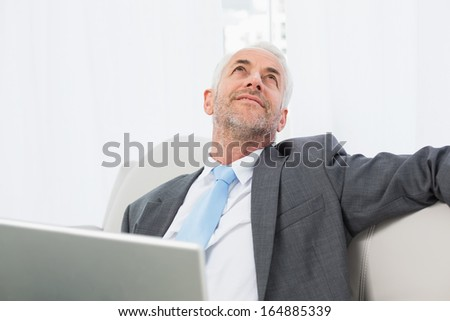 Relaxed mature businessman with laptop sitting on sofa in living room at home