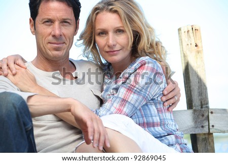 Relaxed mature couple sitting in the sunshine - stock photo