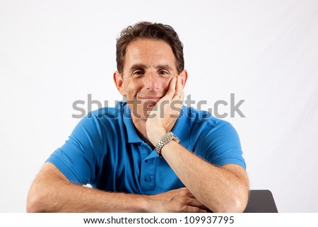 Relaxed mature man holding his hand by his face and with eye contact and a big smile