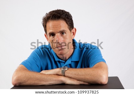 Relaxed mature man with his hands folded on a table before him and a thoughtful, serious expression