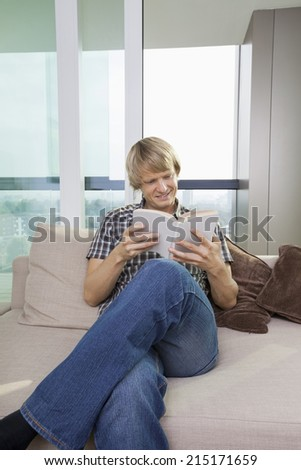 Relaxed mid-adult man reading book in living room at home - stock photo