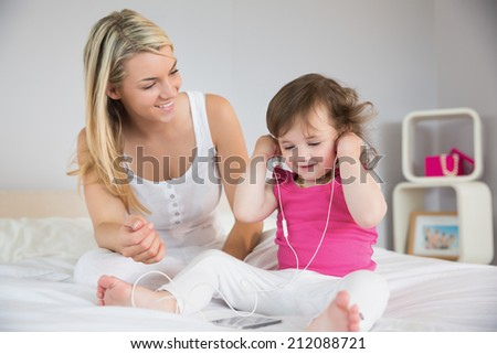 Relaxed mother looking at young daughter with headphones on bed at home
