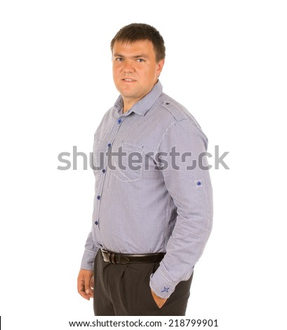Relaxed overweight young man standing sideways with his hand in his pocket looking at the camera, isolated on white