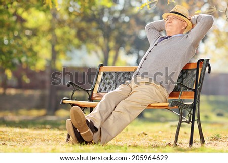 Relaxed pensioner sitting on a bench in park - stock photo