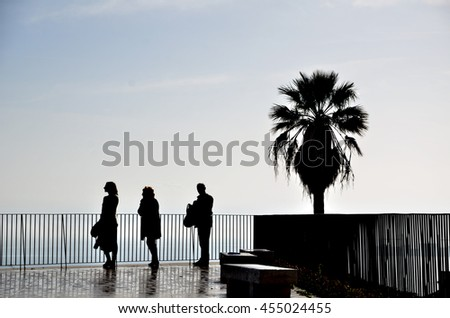 Relaxed people enjoying the view from terrace above the seaside in Lisbon, Portugal. Silhouette shot with copyspace. - stock photo