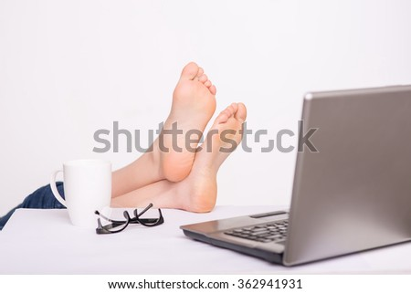 Relaxed person holding legs on the table