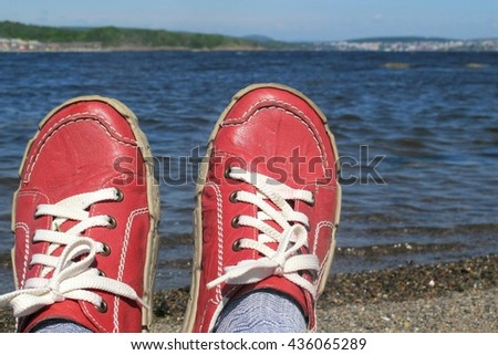 Relaxed person in red shoes  sitting on sandy beach with water in front. - stock photo