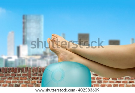 relaxed person with feet above the ball like at the beach on the attic terrace in summertime - stock photo