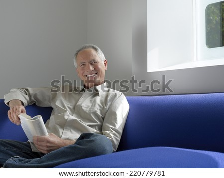 Relaxed portrait of a senior man sitting with a book looking to camera in a contemporary interior - stock photo