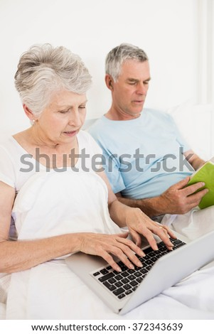 Relaxed senior couple at bed using laptop and reading boook