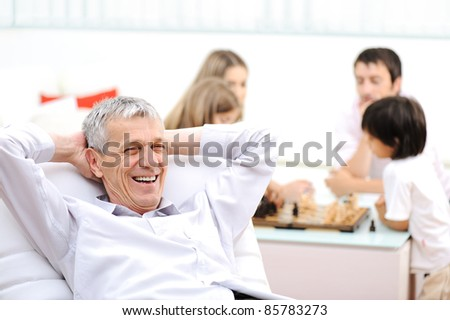 Relaxed senior man on sofa, family in background - stock photo