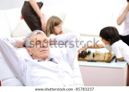 Relaxed senior man on sofa taking a nap, family in background - stock photo
