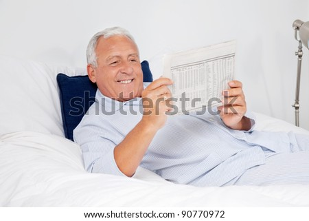 Relaxed senior man reading newspaper while lying on bed at home - stock photo