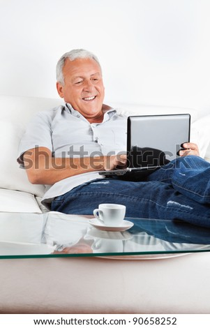 Relaxed senior man sitting on sofa working on laptop at home - stock photo