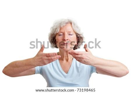 Relaxed senior woman doing some breathing exercises - stock photo