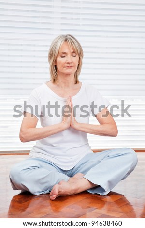 Relaxed senior woman meditating at home on floor - stock photo
