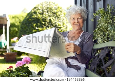 Relaxed senior woman sitting on a bench in backyard garden reading a newspaper looking at camera and smiling - stock photo