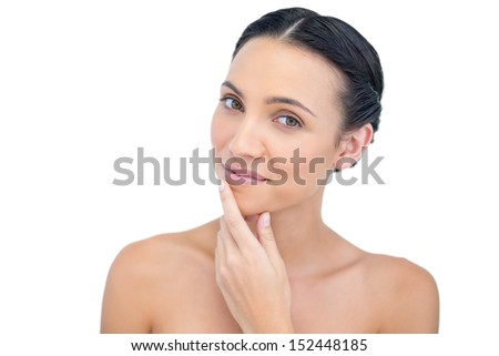 Relaxed sensual model posing with hand on her chin on white background - stock photo