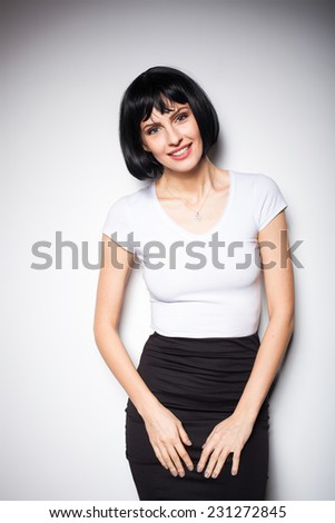 relaxed smiling beautiful woman in black and white outfit standing next to a wall - stock photo