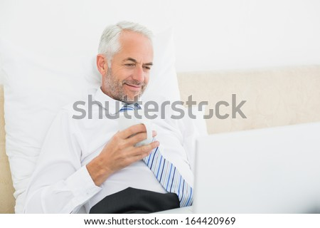 Relaxed smiling mature businessman using laptop while having coffee in bed at home