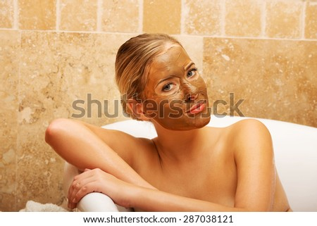 Relaxed spa woman sitting in a bath with face mask - stock photo