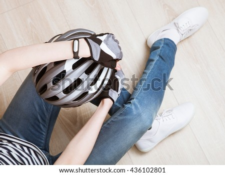 Relaxed sporty young woman sitting on the floor holding bicycle helmet - upper viewpoint - stock photo