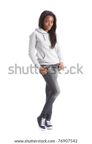 Relaxed standing pose from beautiful young black teenage girl, wearing grey hoodie sweater and blue jeans. Girl has long hair. - stock photo