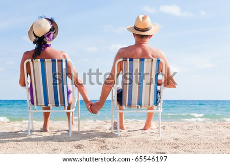 Relaxed summer vacation senior couple of old man and woman sitting on the beach - stock photo