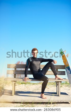 Relaxed surfer in his wetsuit waiting on a wooden bench on a platform on top of a coastal sand-dune with his surfboard propped up alongside him under a clear blue sunny summer sky with copyspace - stock photo