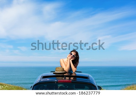 Relaxed tranquil woman on summer travel vacation to the coast  leaning out car sunroof with the sea on background. - stock photo