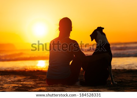 Relaxed woman and dog enjoying summer sunset or sunrise over the sea sitting on the sand at the beach. - stock photo