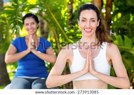 Relaxed woman and her trainer doing yoga on a sunny day - stock photo