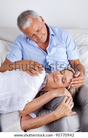 Relaxed woman asleep on husband's lap - stock photo